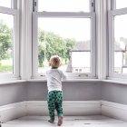 Kleiner Junge schaut zu Hause aus dem Fenster — Stockfoto