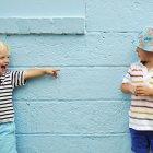 Due ragazzi caucasici in piedi accanto al muro, uno puntato su un altro — Foto stock