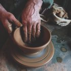 Cropped image of person making pottery indoors — Stock Photo