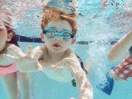 Мальчик, плавание под водой с друзьями — стоковое фото