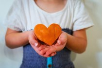 Cropped image of Girl holding heart shaped pumpkin — Stock Photo