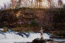 Jeune garçon jetant des pierres dans une cascade — Photo de stock