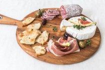 Сыр и измельченное мясо на доске — стоковое фото
