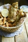 Basket with fish and chips over wooden table — Stock Photo