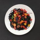Massa de tinta de lula preta com tomate fresco e manjericão — Fotografia de Stock