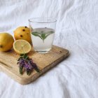Lemon and mint water over chopping board — Stock Photo