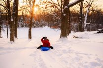 Хлопчик ковзає вниз на заході сонця — стокове фото