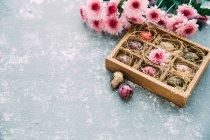 Huevos de Pascua multicolores y flores sobre fondo rústico - foto de stock