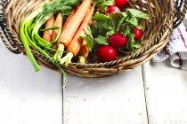 Свіжі овочі в кошику над дерев'яний стіл — стокове фото