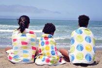 Trois filles assises sur la plage enveloppées dans des serviettes — Photo de stock