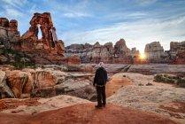 Человек, смотрящий на арку Друидов на закате, Национальный парк Каньонлендс, Юта, Америка, США — стоковое фото