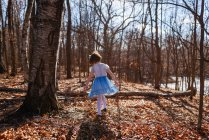 Girl in a dress walking through forest — Stock Photo