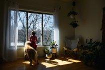 Девушка и ее золотая собака-ретривер смотрят в окно — стоковое фото