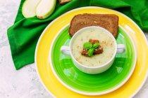 Суп из цуккини с ржаным хлебом на цветных тарелках — стоковое фото