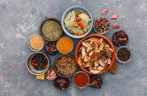 Herbs and spices in bowls over marble table, top view — Stock Photo