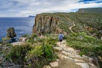Людина Піші прогулянки по відношенню до Fortescue Bay, Мис Hauy, Тасманія, Австралія — стокове фото