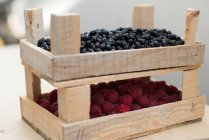 Crates of fresh raspberries and blueberries, selective focus — Stock Photo