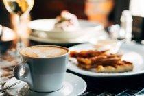 Чашка горячего кофе и печенье над деревянным столом, вид крупным планом — стоковое фото