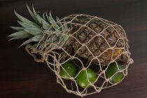 Closeup view of Pineapple and limes in a mesh bag — Stock Photo