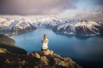 Жінка сидить на скелі і дивиться на озеро Гарібальді (Британська Колумбія, Канада). — стокове фото