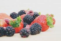 Morangos, amoras-pretas e framboesas sobre uma tábua — Fotografia de Stock
