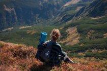 Woman sitting on mountain slope taking a photo, Ukraine — Stock Photo