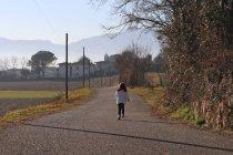 Девушка бежит по проселочной дороге — стоковое фото