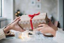 Image recadrée de femmes donnant à son ami un cadeau de Noël enveloppé — Photo de stock