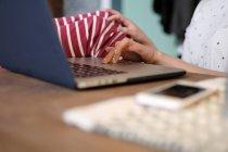 Mujer sentada en una mesa usando su computadora portátil, recortada - foto de stock