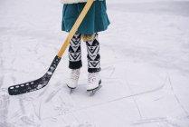 Cierre de las piernas de una niña jugando al hockey de hielo - foto de stock