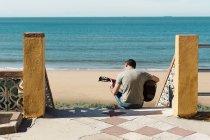 Uomo seduto sui gradini vicino alla spiaggia a suonare la chitarra, Spagna — Foto stock