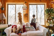 Boy and golden retriever dog standing on couch looking out of the window — Stock Photo