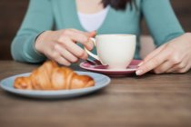 Woman holding cup of coffee, fresh croissant on a plate — Stock Photo