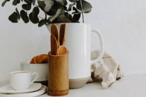 Coffee cup, croissant, Kitchen utensils and eucalyptus in a jug — Stock Photo