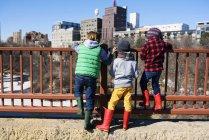 Trois enfants debout sur le pont Stone Arch regardant le paysage urbain, Minneapolis, Minnesota, Amérique, USA — Photo de stock