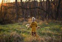 Girl standing in the woods watching her dog running around, United States — Stock Photo