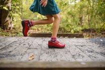 Chica corriendo a través de una pequeña pasarela, Estados Unidos - foto de stock