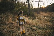Boy standing in the woods in autumn, United States — Stock Photo