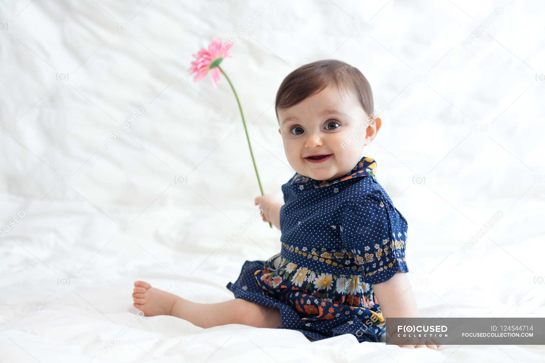 b3867554cc Baby girl playing with flower — white background