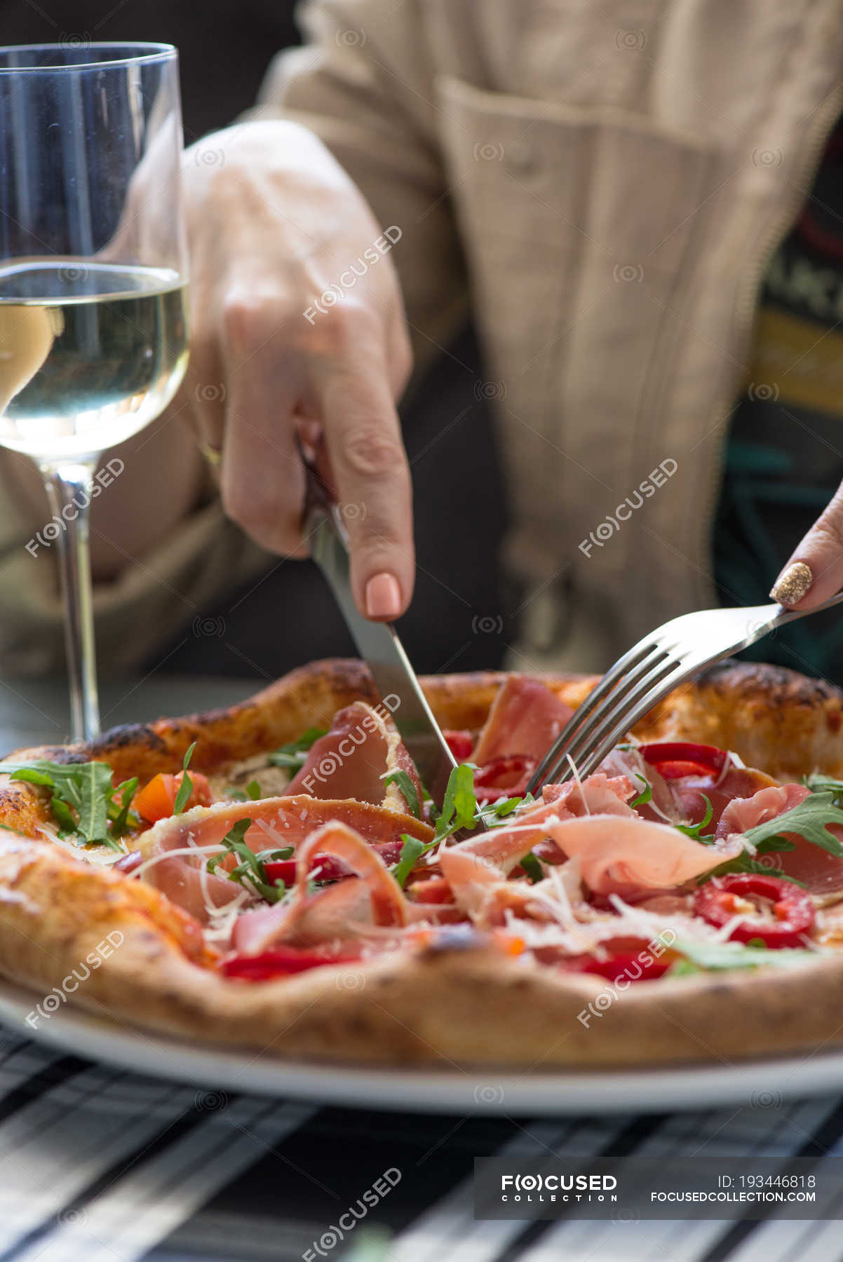 Female Hands Cutting Off A Piece Of Delicious Pizza And Glass Of