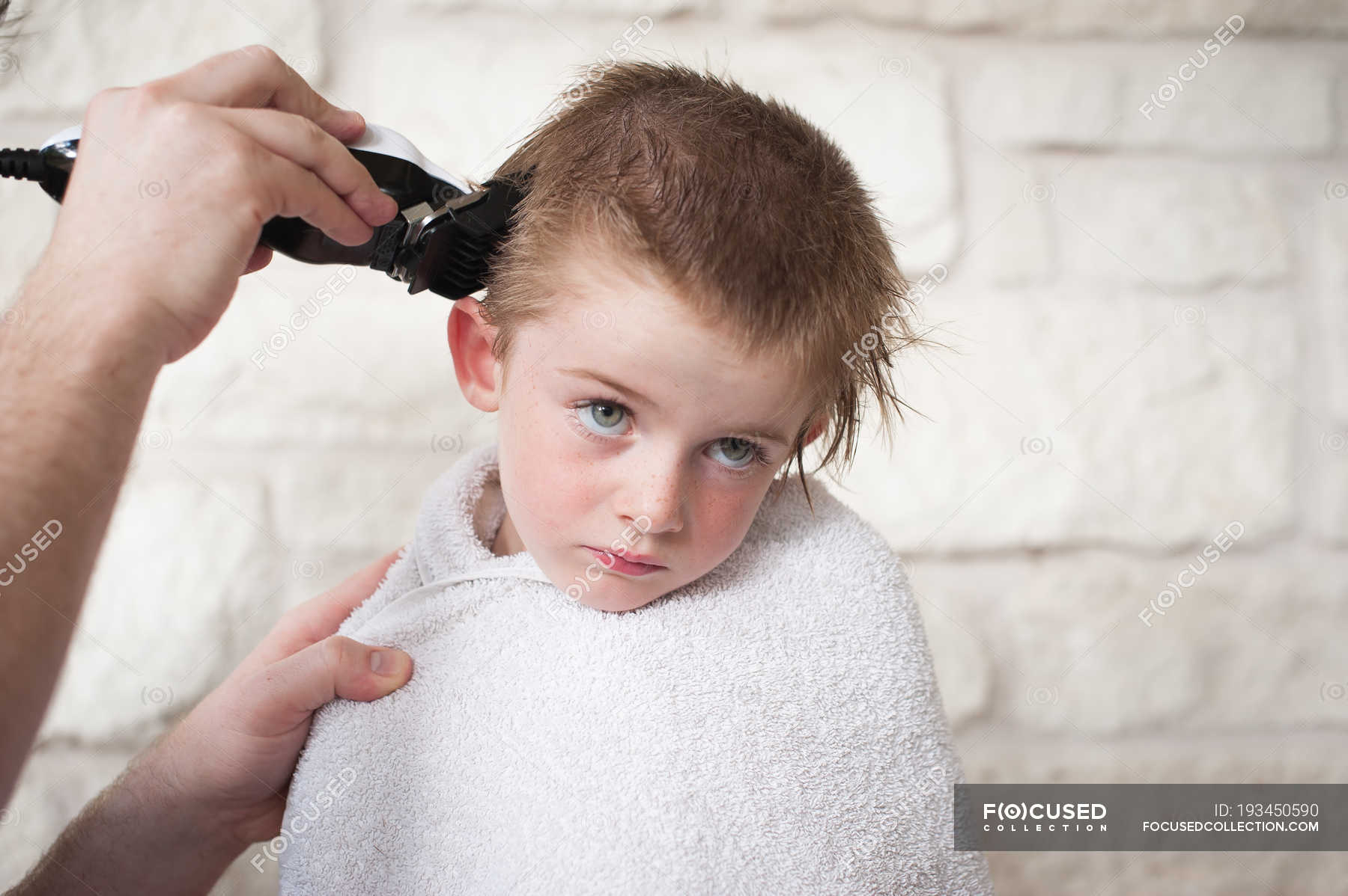 boy getting a buzz haircut by his father stock photo 193450590