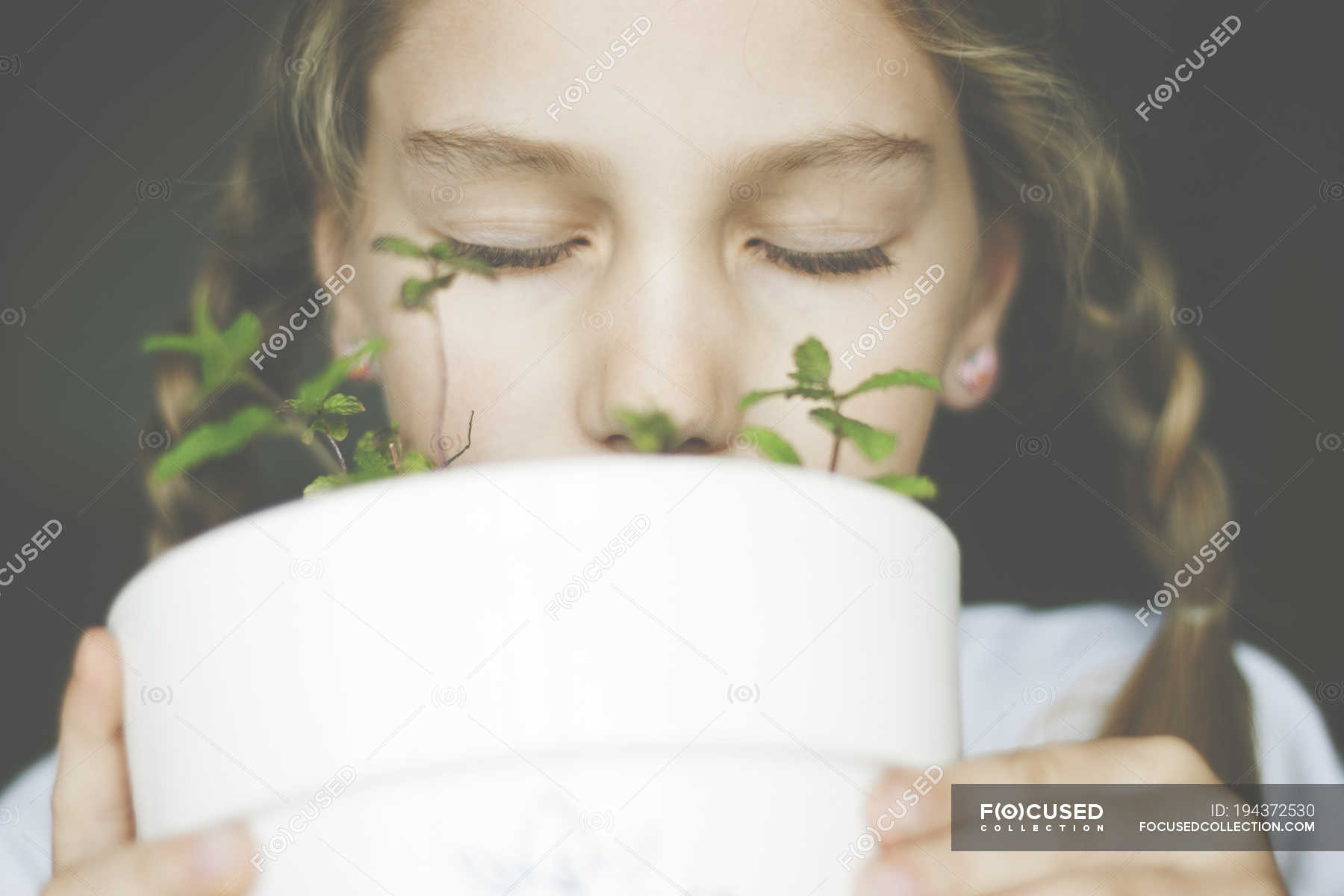 Girl smelling mint plant in a plant pot — front view, elementary age