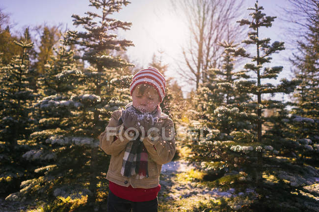 Boy blowing handful of snow — Stock Photo