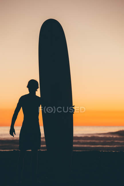Surfer standing on beach with surfboard — Stock Photo