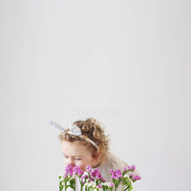 Girl in bunny ears smelling flowers — Stock Photo
