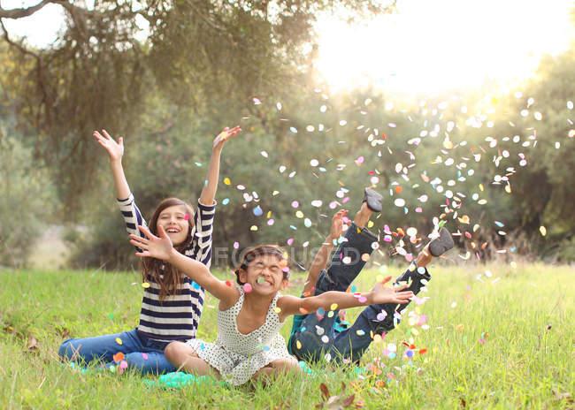 Three children throwing confetti in air — Stock Photo