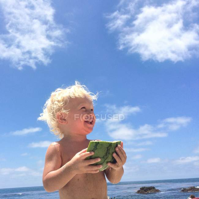 Toddler boy holding piece of watermelon — Stock Photo