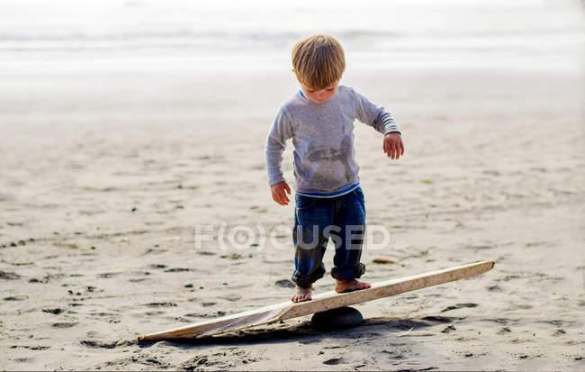 Мальчик балансирует на деревянной доске — стоковое фото