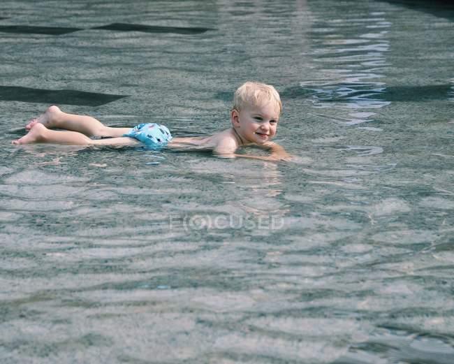 Junge liegt im Wasser — Stockfoto