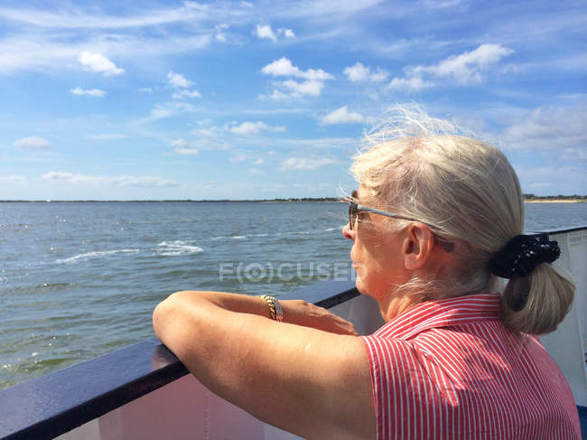 Woman on boat looking out to sea — Stock Photo